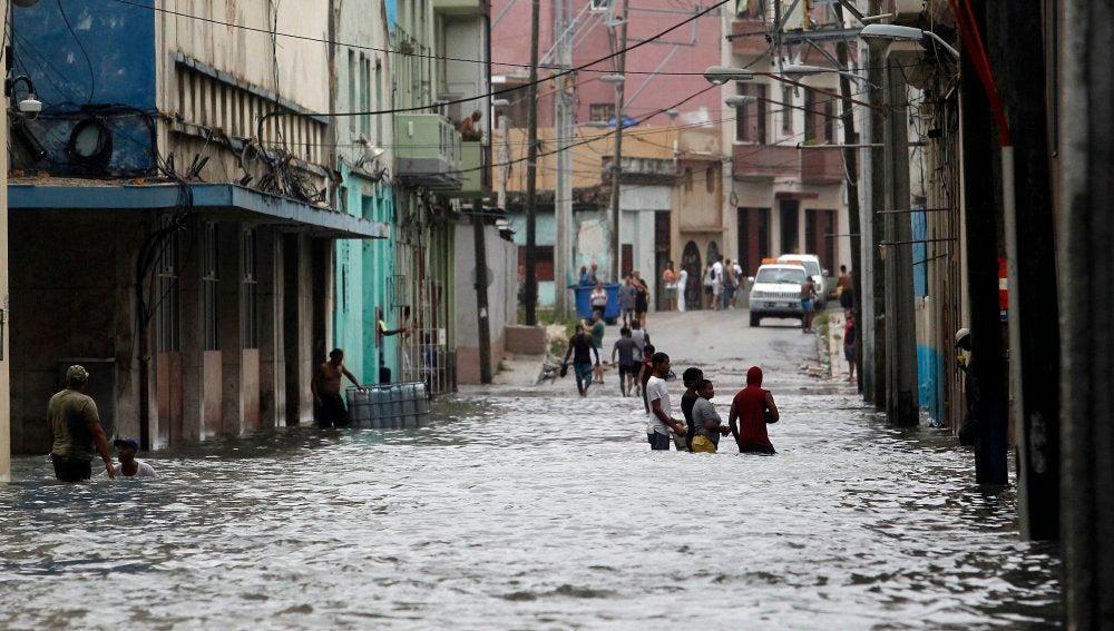 Varias personas caminan dentro del agua en una calle inundada de la capital cubana