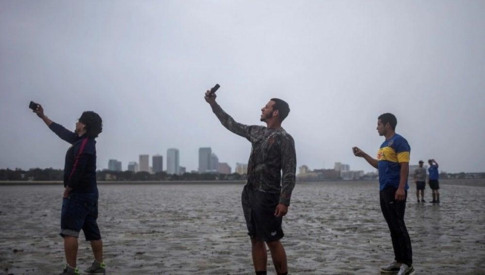 Varias personas se hacen selfies en la costa con el mar retirado