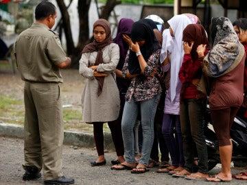 Policía de la sharía aleccionando a unas jóvenes, en Indonesia