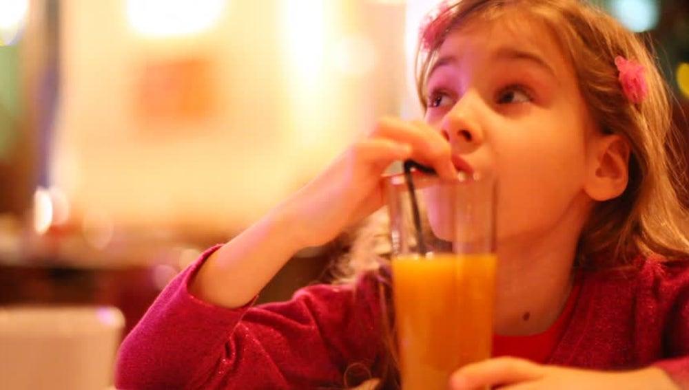 Niña bebiendo zumo con una pajita