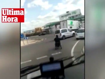 Una persona circula por medio de una vía pública  en silla de ruedas motorizada