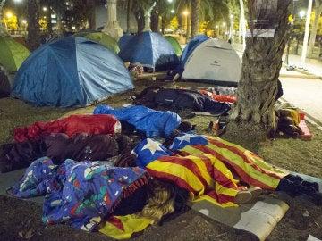Varias personas duermen frente a la sede del Tribunal Superior de Justicia de Cataluña (TSJC), donde esta noche han acampado entre 200 y 300 personas en protesta por la detención de 14 altos cargos del Govern, técnicos de la Generalitat y directivos de empresas, por la organización del referéndum del 1-O, que ha sido suspendido por el Tribunal Constitucional