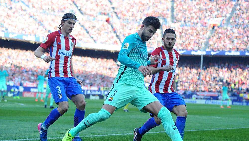 Piqué intenta despejar el balón ante la presión de Filipe Luis y Koke