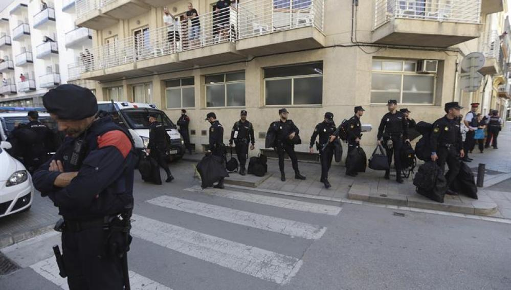 Un grupo de policías nacionales espera su transporte delante del hotel Mont-Palau de Pineda