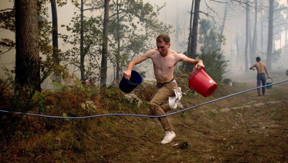Los vecinos tratan de apagar el fuego con cubos