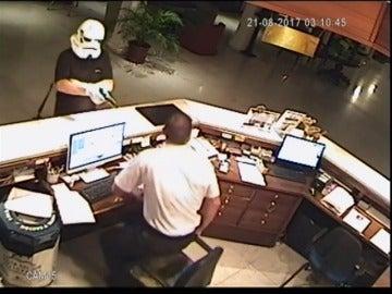 Un hombre, disfrazado con una máscara de la Guerra de las Galaxias, atraca a punta de pistola al recepcionista de un hotel