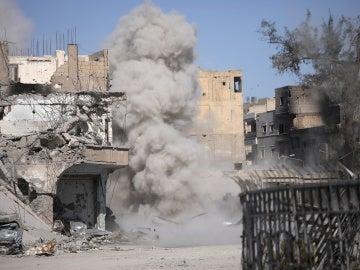 El humo se levanta después de que una mina terrestre explotara mientras los combatientes de las Fuerzas Democráticas Sirias limpian los caminos de Raqqa