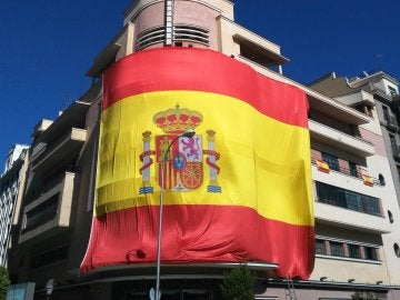 Gran bandera de España colgada en la fachada del Teatro Barceló