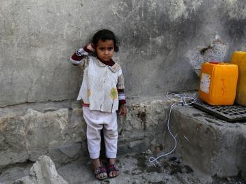 Una niña yemení espera para llenar sus garrafas de agua potable en Saná