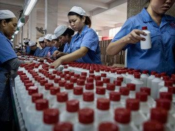 Trabajadores chinos organizando botellas de baijiu