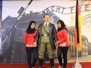 Dos mujeres haciéndose una foto con la estatua de Hitler