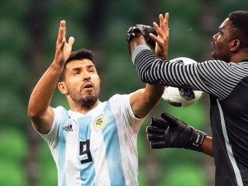 Akpeyi intenta atrapar un balón ante la presión de Agüero