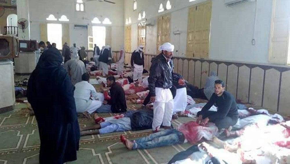 Varias personas permanecen junto a cuerpos sin vida en el interior de la mezquita atacada en Egipto