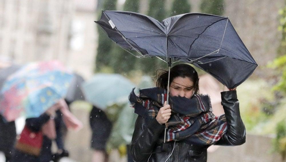 Una mujer combate los fuertes vientos y la lluvia
