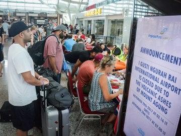 Turistas escuchan información sobre sus vuelos tras la erupción del volcán Agung en el aeropuerto Ngurah Rai en Denpasar en Bali (Indonesia)