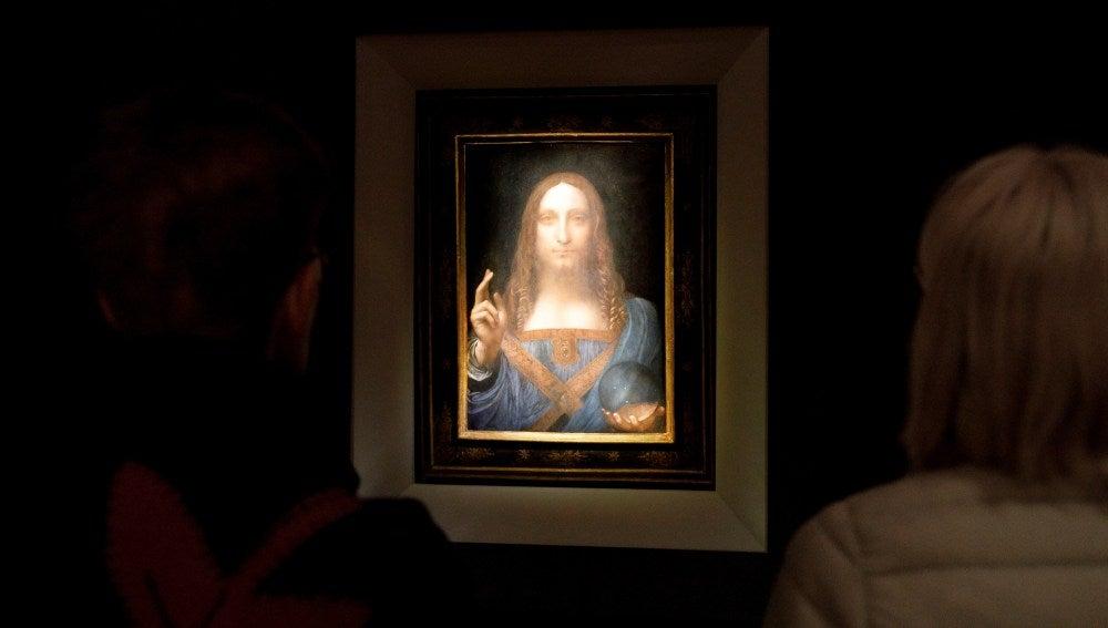 Varias personas observan la obra 'Salvator Mundi' del artista Leonardo da Vinci