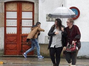 Vecinos de Melide se protegen de la lluvia y el viento