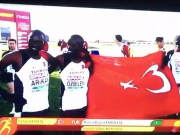 Atletas nacionalizados turcos posan con la bandera de Turquía del revés