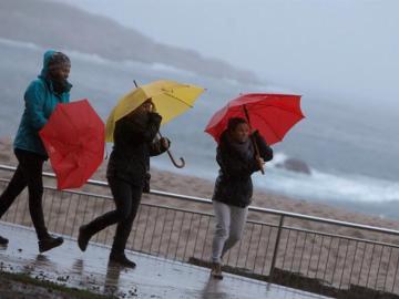 Tres mujeres se protegen de la lluvia en el paseo marítimo de A Coruña