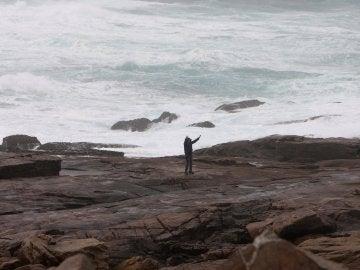Dos personas se fotografían junto al oleaje en la zona de Cabo Silleiro