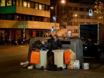 Un hombre buscando entre la basura