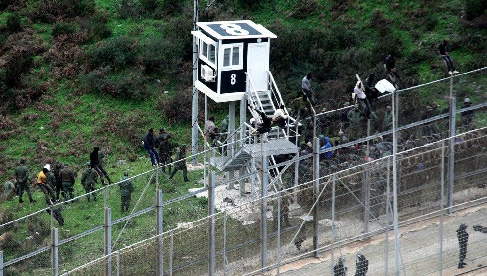 Algunos de los 800 inmigrantes custodiados por la policía marroquí junto a la valla del perímetro fronterizo de Ceuta