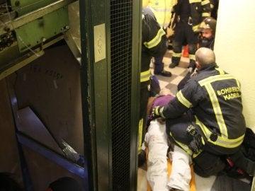 Los bomberos atienden a una de las heridas tras descolgarse el ascensor