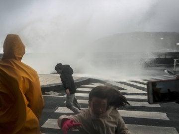 Varias personas son sorprendidas por una ola en el Paseo Nuevo de San Sebastián
