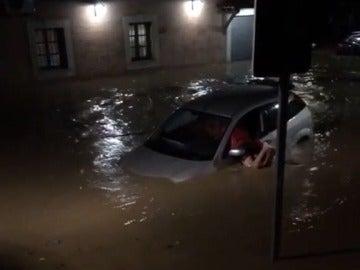 Un hombre intenta salir de su coche, atrapado por la riada