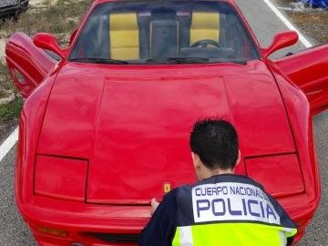 Un agente de la Policía Nacional junto al vehículo modificado para ser vendido como un Ferrari
