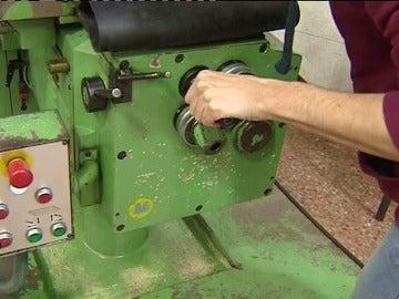 Un trabajador manipula una máquina en una fábrica
