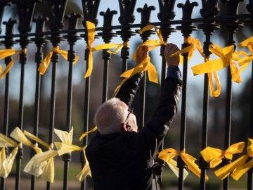 Un hombre coloca lazos amarillos en la verja del Pac de la Ciutadella (Archivo)