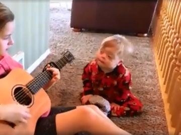 Una niña canta a su hermano con síndrome de Down