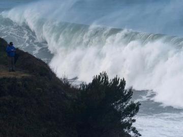 Un hombre fotografía las grandes olas que rompen ayer en la costa de la capital cántabra