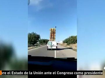 Identifican a un conductor por transportar una veintena de palés en el techo de su furgoneta