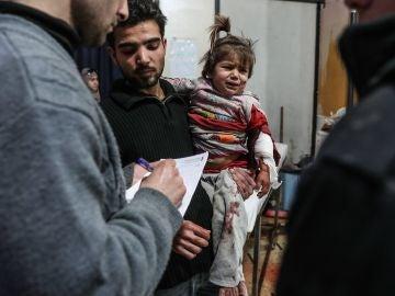 Una niña herida recibe atención médica después de bombardeos