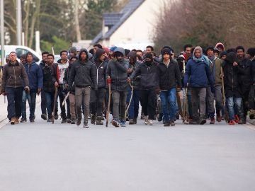 Un grupo de inmigrantes carga palos y piedras durante un enfrentamiento