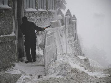 Un hombre retira la nieve de la puerta de una vivienda