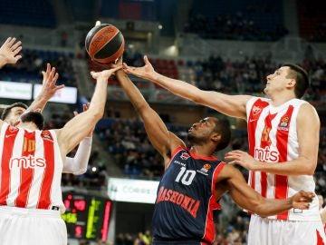 Rodrigue Beaubois intenta capturar el balón ante los jugadores del Estrella Roja