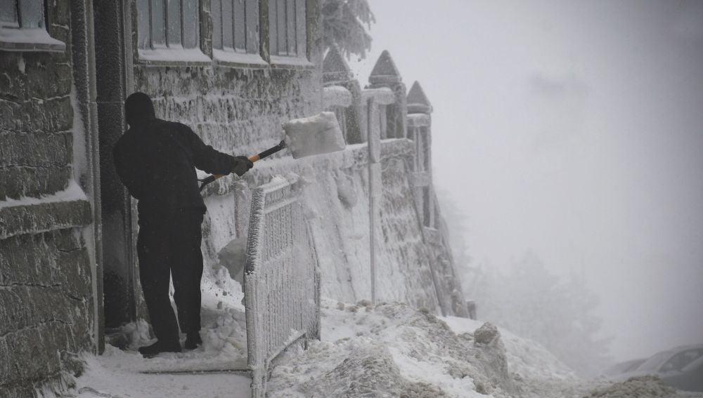 Un hombre retira la nieve de la puerta de una vivienda esta mañana en el Puerto de Navacerrada