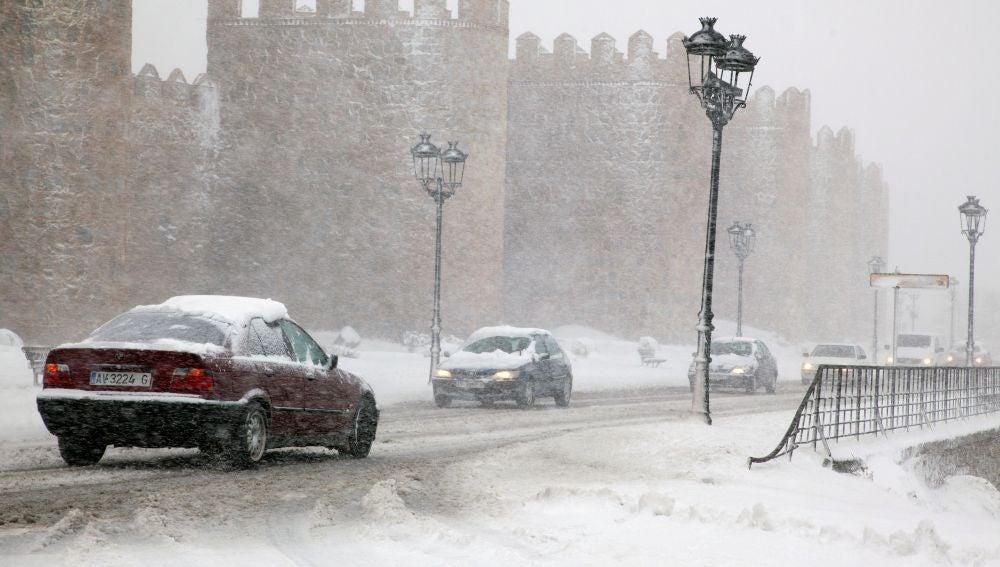 Varios vehículos circulan por una carretera próxima a la muralla de Ávila