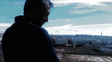 """Fotomontaje titulado """"La soledad"""". La autora es Laura Rico. Se ve de fondo un paisaje urbano frío y azulado. Y en primer término, de espaldas, la silueta a contraluz de un hombre que mira al suelo con aspecto triste."""
