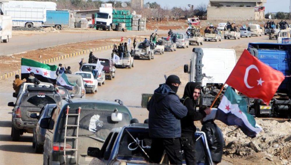 Miembros del Ejército Libre Sirio circulan junto a tropas turcas en la ciudad de Azez, en la zona siria de Afrín