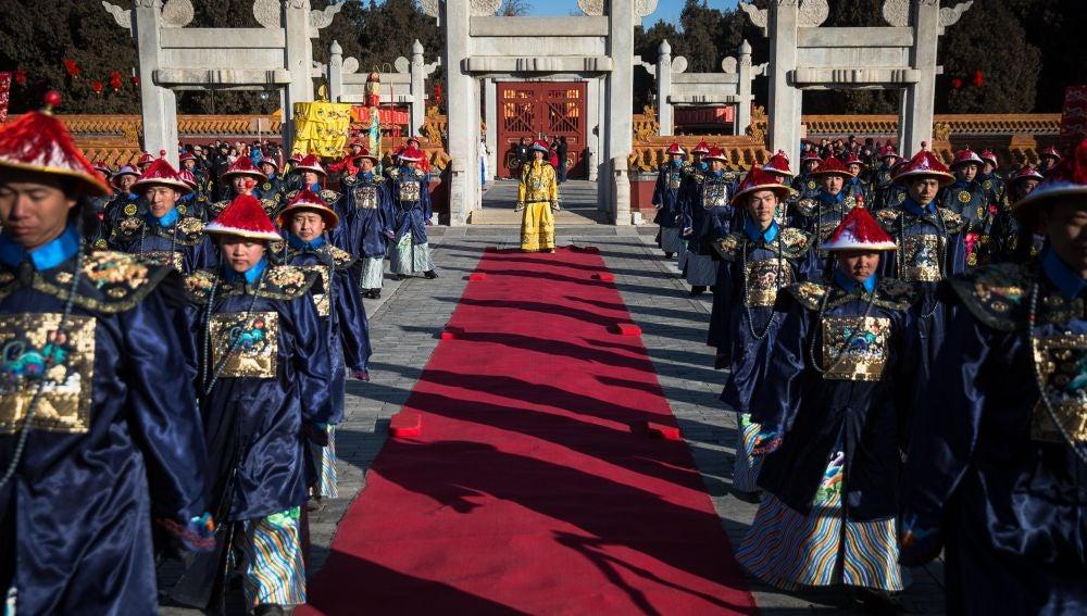 Artistas chinos vestidos con trajes tradicionales realizan una recreación de un ritual