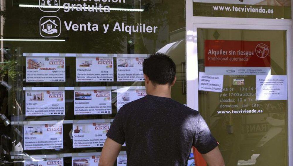 Un hombre mira los pisos en venta de una inmobiliaria