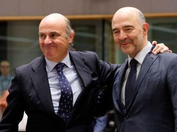 El ministro español de Economía, Luis de Guindos, saluda al comisario europeo de Economía y Asuntos Financieros, Pierre Moscovici