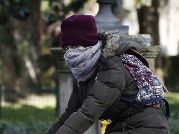 Una joven montada en su bicicleta se protege del frío