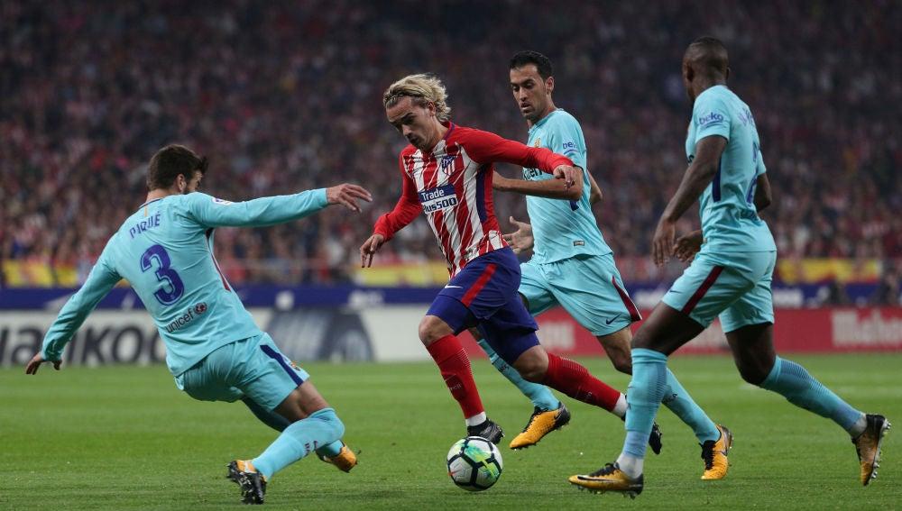Griezmann intenta avanzar ante la defensa del Barcelona