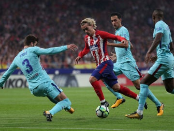 Griezmann intenta avanzar ante la defensa del Barcelona