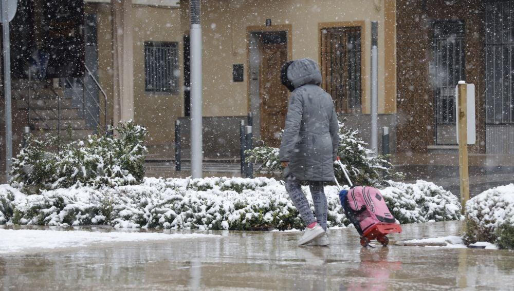 Una mujer camina bajo la nieve que desde esta mañana cae sobre Utiel